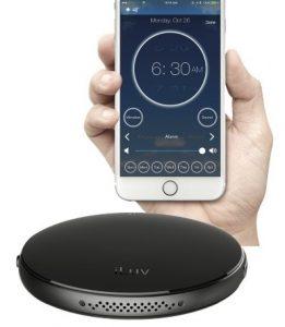 En iPhone med en app där det står vilken tid alarmet ska gå samt en lite större, rund trådlös vibrator