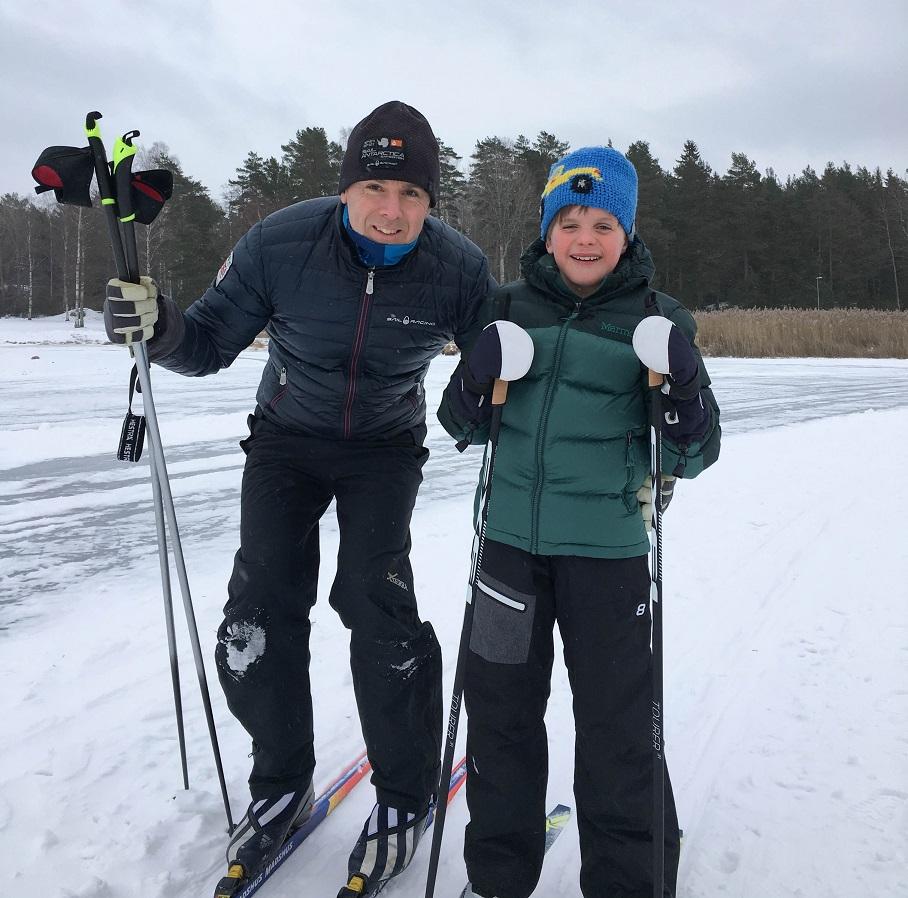 Pappa till vänstre och Oliver tillhöger. Båda står på skidor.