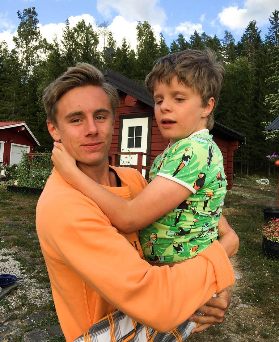 Oskar, kortklippt med oragne trja har Oliver i grönmönstrad, kortärmad tröja i famnen.