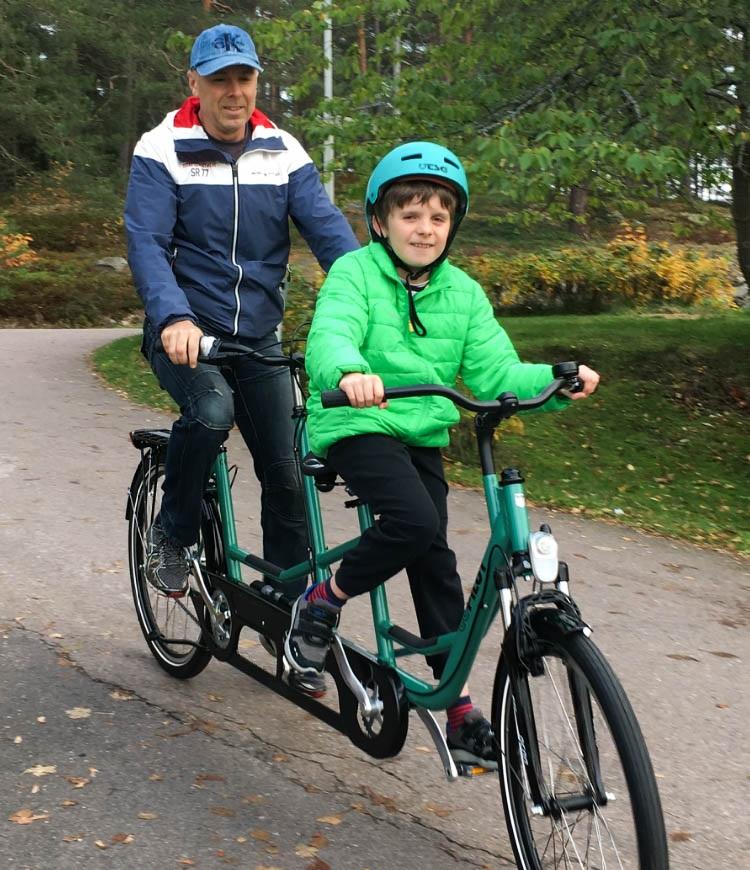 Oliver i grön jacka och cykelhjälm längst fram på tandemcykeln. Pappa är bakom.