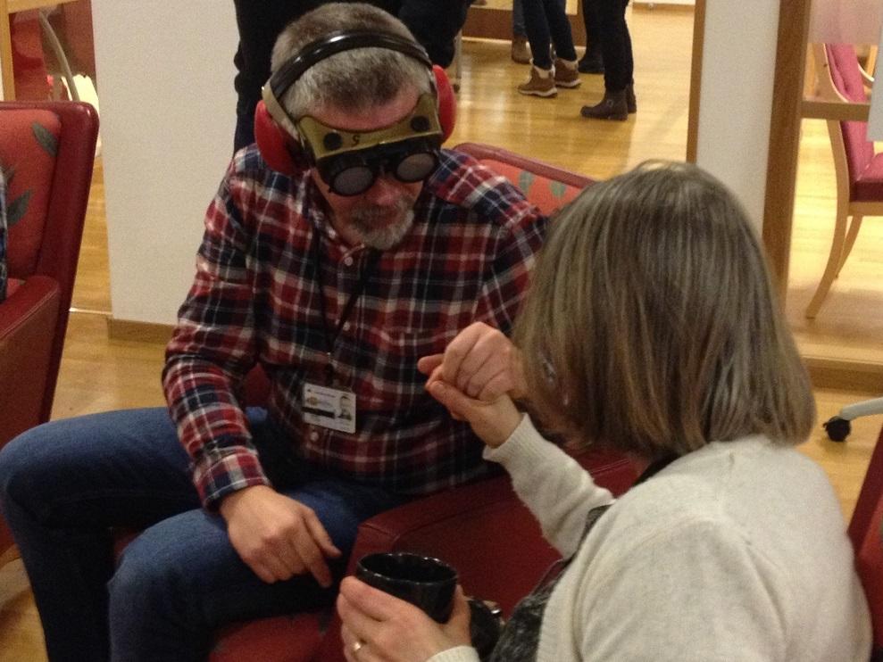 En man i rutig skjorta och jeans med fingerad optik och hörselkåpor håller en kvinna med axellångt hår och ljus ströja i handen. Hon har en kaffekopp i sin andra hand.