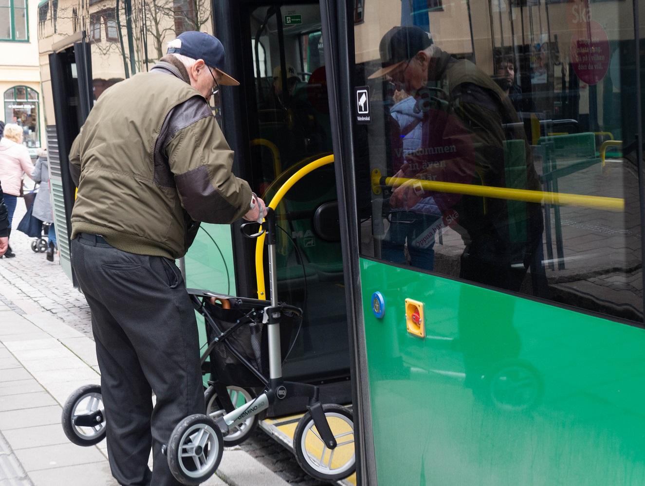 en man i keps lyfter sin rullator ombord på en grön buss