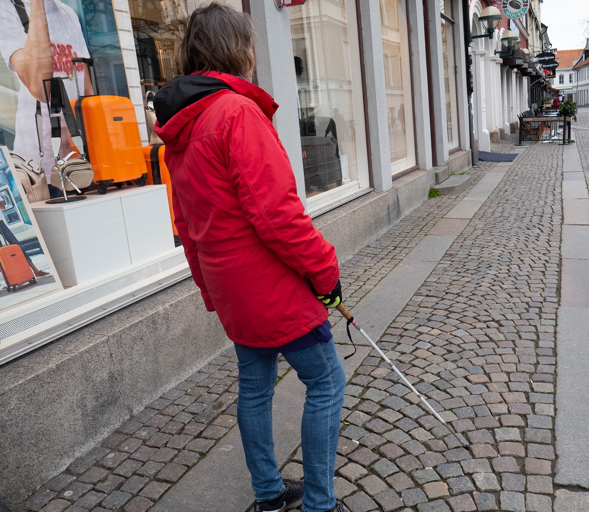 Kvinnani röd jacka och jeans med vit käpp står på en gata, fotograferad bakifrån
