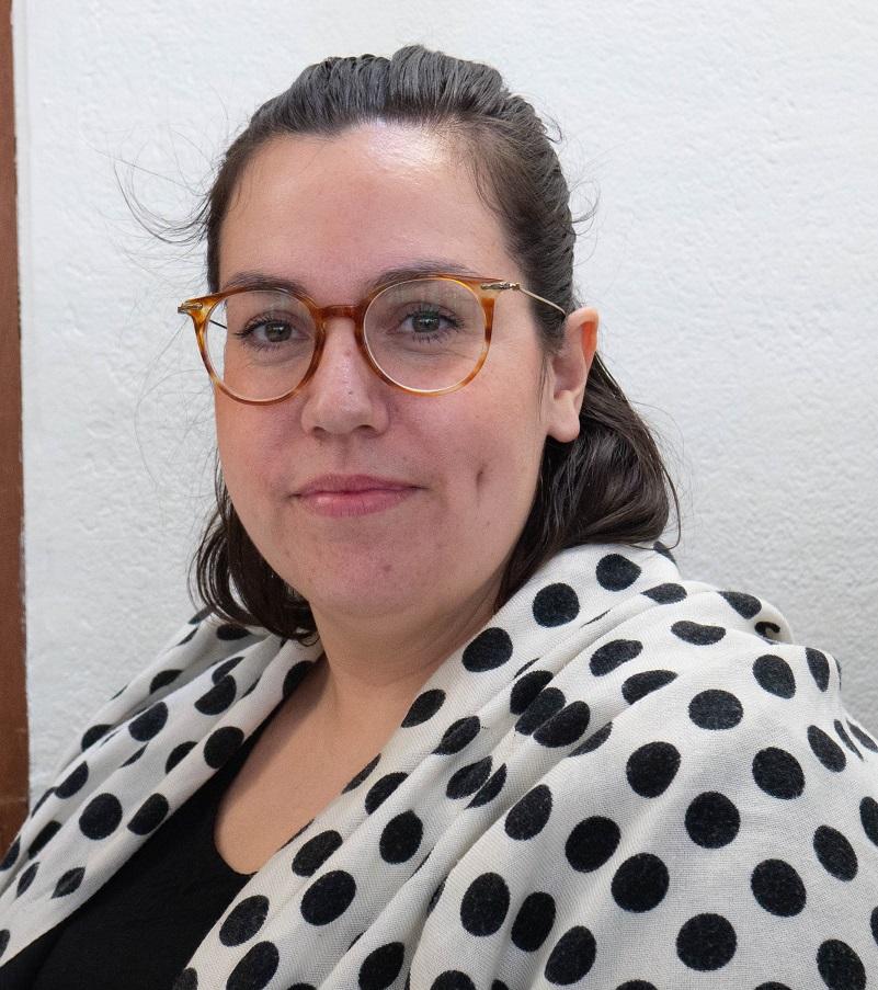 mörkt hår bakåtkammat, sköldpaddsmönstrade glasögon, vit tröja med svarta prickar