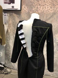 En svart klänning med blixtlåset i ryggen öppnat så man kan se att det finns vita fickor på insidan