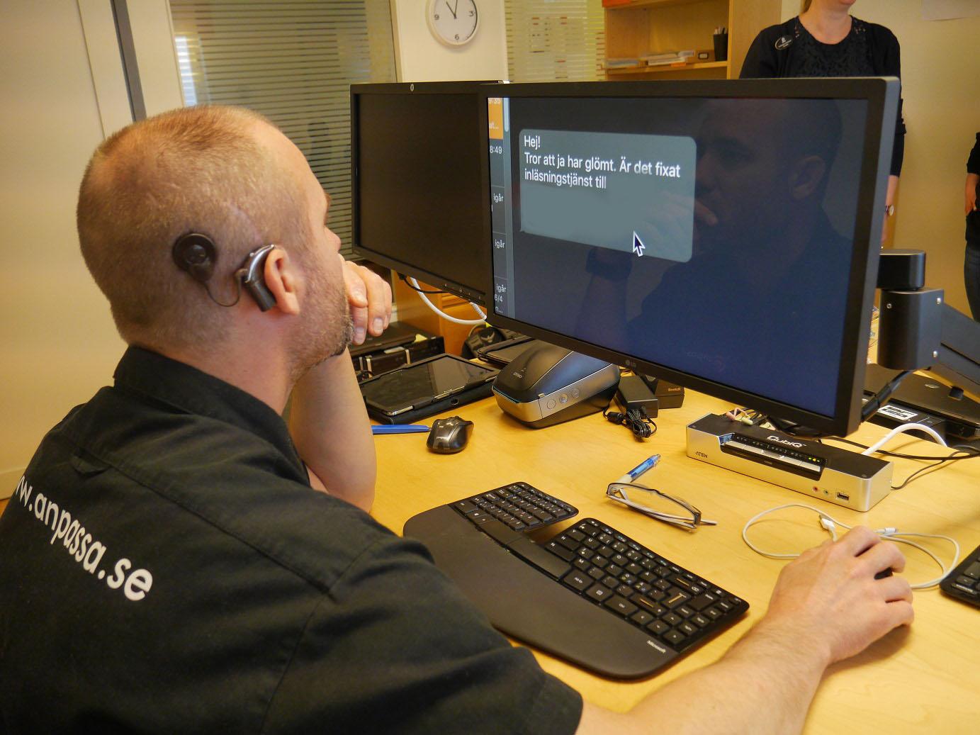 En person med dövblindhet fotad bakfirån. Han har CI och är klädd i svart tröja och sitter framför en dator med förstorad text.