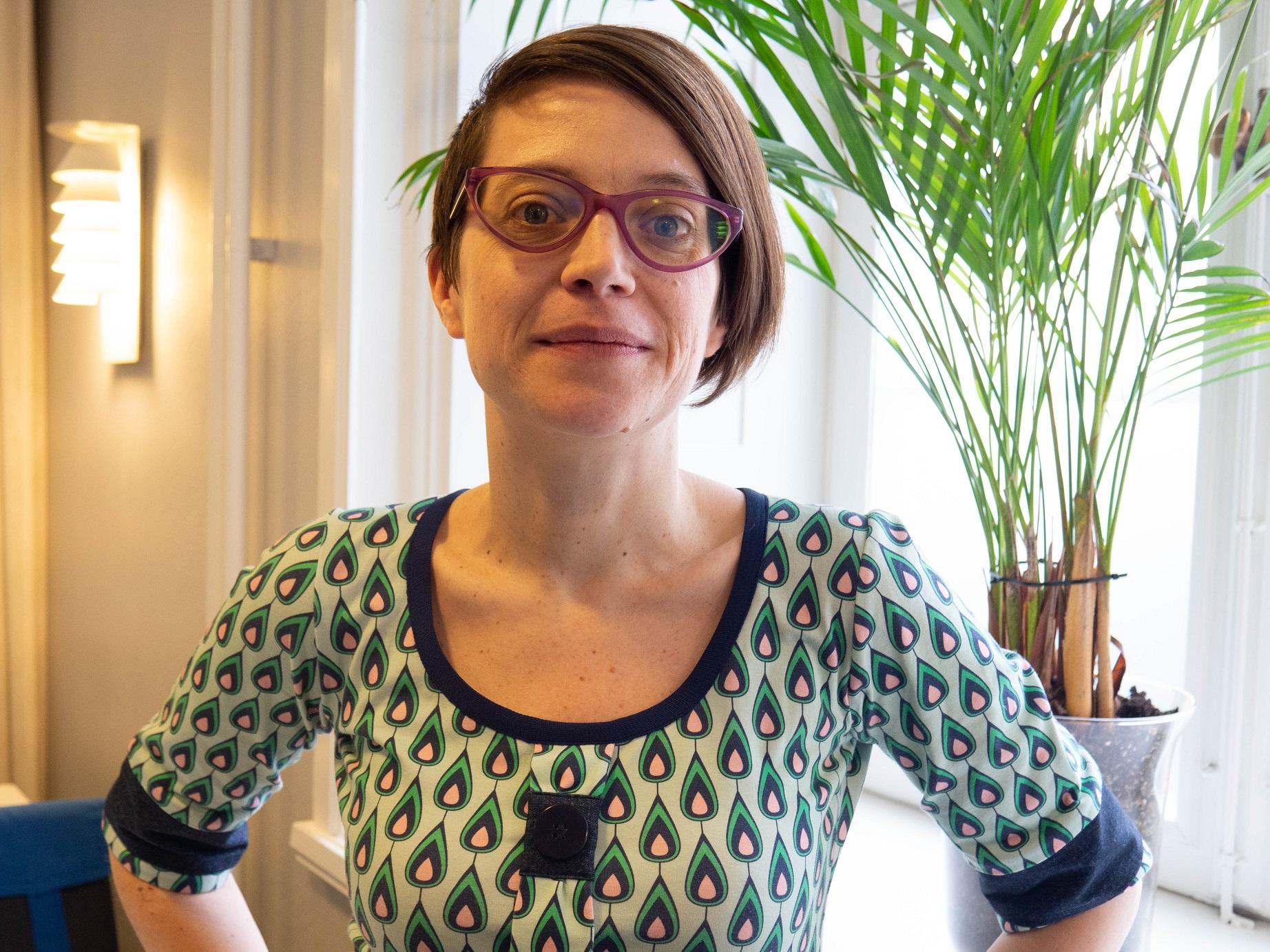 Tove ser bestämd ut och har händerna i midjan. Kort brunt hår, stora glasögomn och en klänning med grafiskt formade dropper i grönt, rosa svart mot en ljusgrön botten.