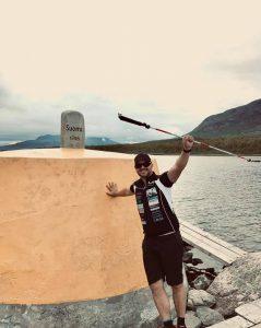 Torbjörn Svensson, med svarta cykelkläder och solglasögon på sig, står vid Treriksröset och lyfter sin vita käpp i luften.