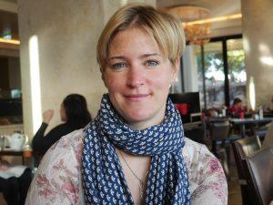 Portrtt Andera i kort ljust hår med mittbena, Hon ler och har en blåprickig sjal runt halsen.