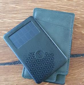 En grån plånbok med ett lite tjockare svart smart kort med soceller ovanpå