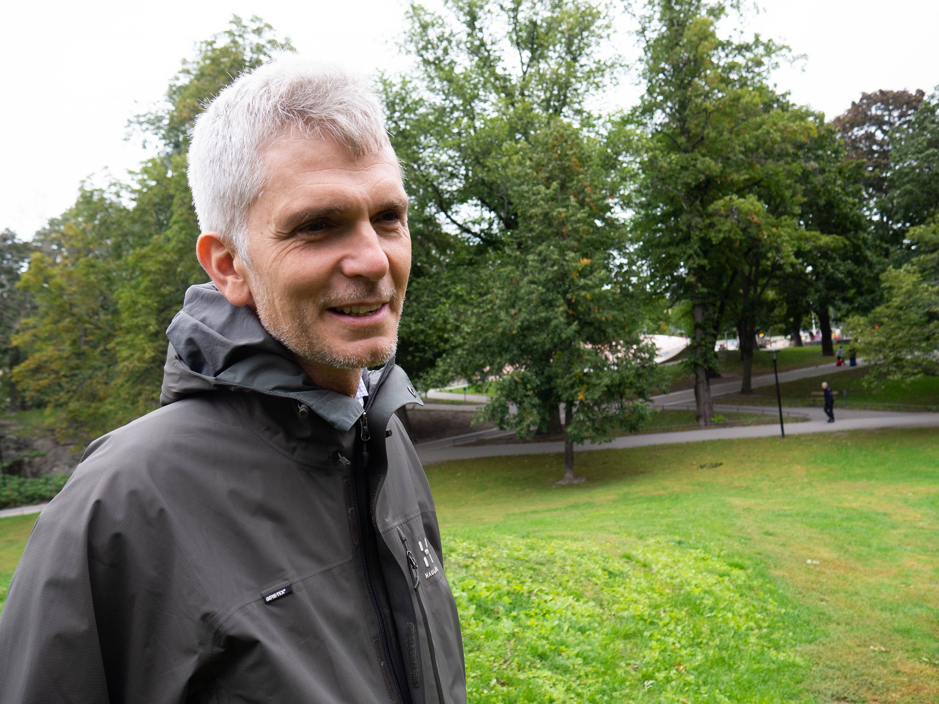 M i vitt hår och grå sportjackatill vänster bild tagen i en åark
