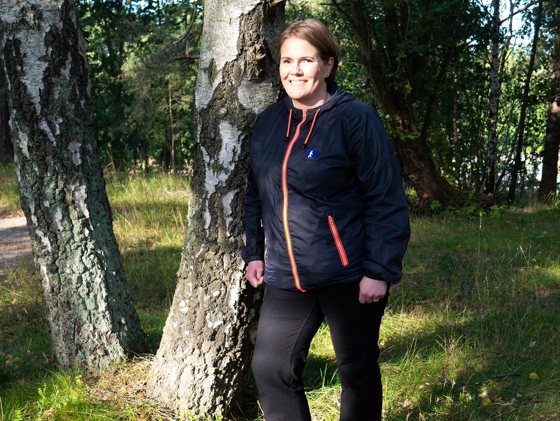 Karen i blå jacka med rött blixtlås står lutad mot en björk i en solig skog.