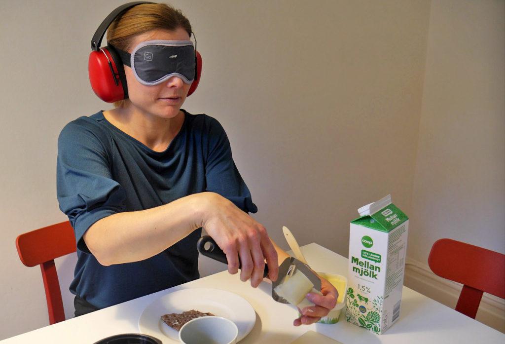 kvinna med ögonbindel och hörselkåpa hyvlar ost.