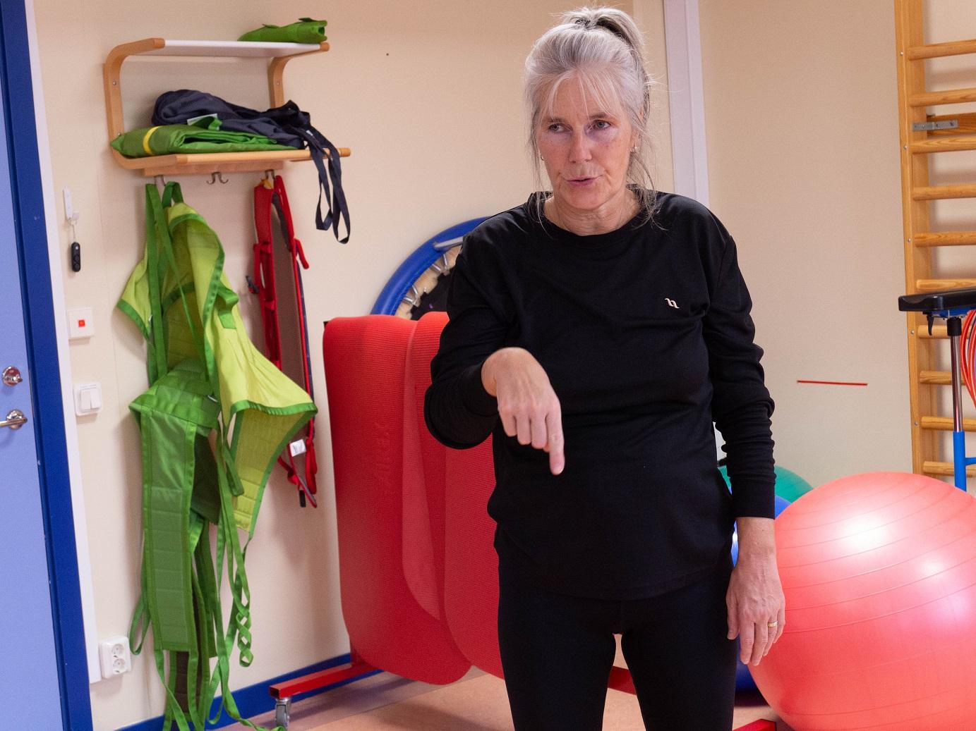 Catarina i svarta kläder instruerar. I bakgrunden olika gymparedskap i grönt, rött och orange.