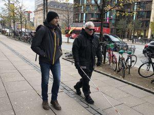 Foto av Frazier och Ulf i Köpenhamn. Ulf har mörka glasögon, Bose frames, och en vit käpp med röda markeringar