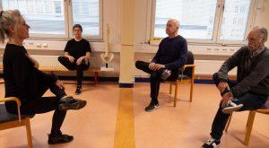 Deltagarna sitter på varsin stol och stretchar benen.