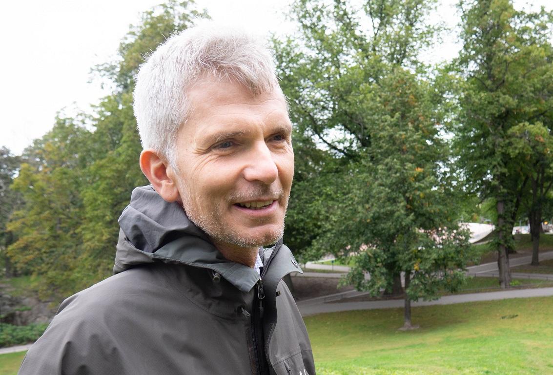 M till vänster i bild, vitt hår grå regnjacka, står i park och ler