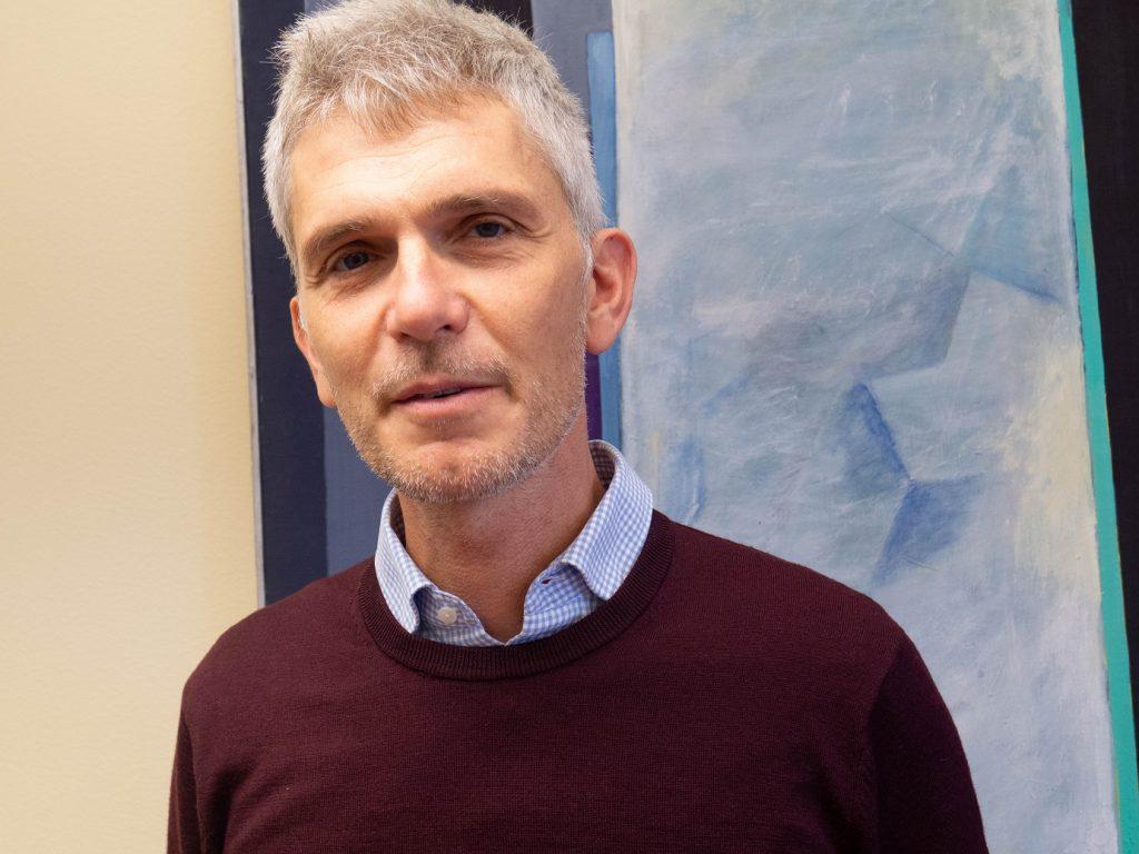 porträtt Mattias Ehn, vinröjd tröja, ljusblå skjortkrage.