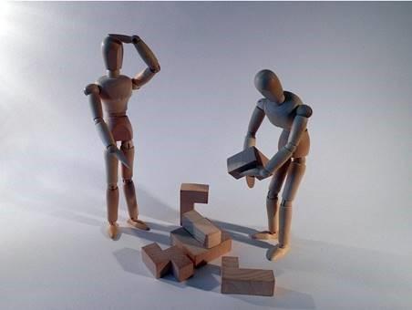 två dockor står mitt emot varandra. Den ene kliar sig i huvdet. Den till höger lyfter en kloss. Mellan dem fler klossar som nog ska fås att sitta ihop.