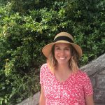 Kristina sler i solhatt och rosa-vit v-tringad kläännning i en trappa. I bakgrunden gröna växter.