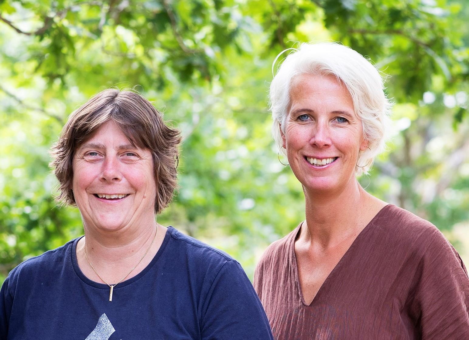 Karin till vänstr i kort, brunt hår och blå tröja. jenny till höger, ljust hår, brunt V-ringat plagg mot en bakgrund av gröna träd.