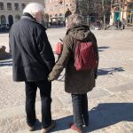 ett äldre par, han i vitt hår och grå jacka till vänster, hon i brun kappa och rosaröd ryggsäck i vänster fotade bakifrån. De håller varann i hand.
