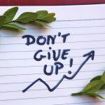 """foto: Handskriven text """"don't give up"""" och två kvistar med gröna blad."""