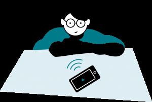 en vibrerande mobiltelefon som ligger på ett bord framför en kvinna med glasögon