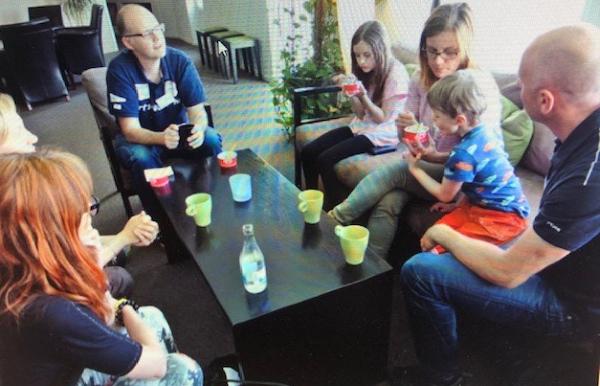 foto: barn och vuxna som fikar runt ett svart soffbord