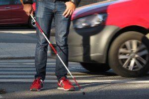 Ett foto där man ser benen på en person som håller i en vit käpp med röda markeringar. I bakgrunden syns en bil och ett övergångsställe.