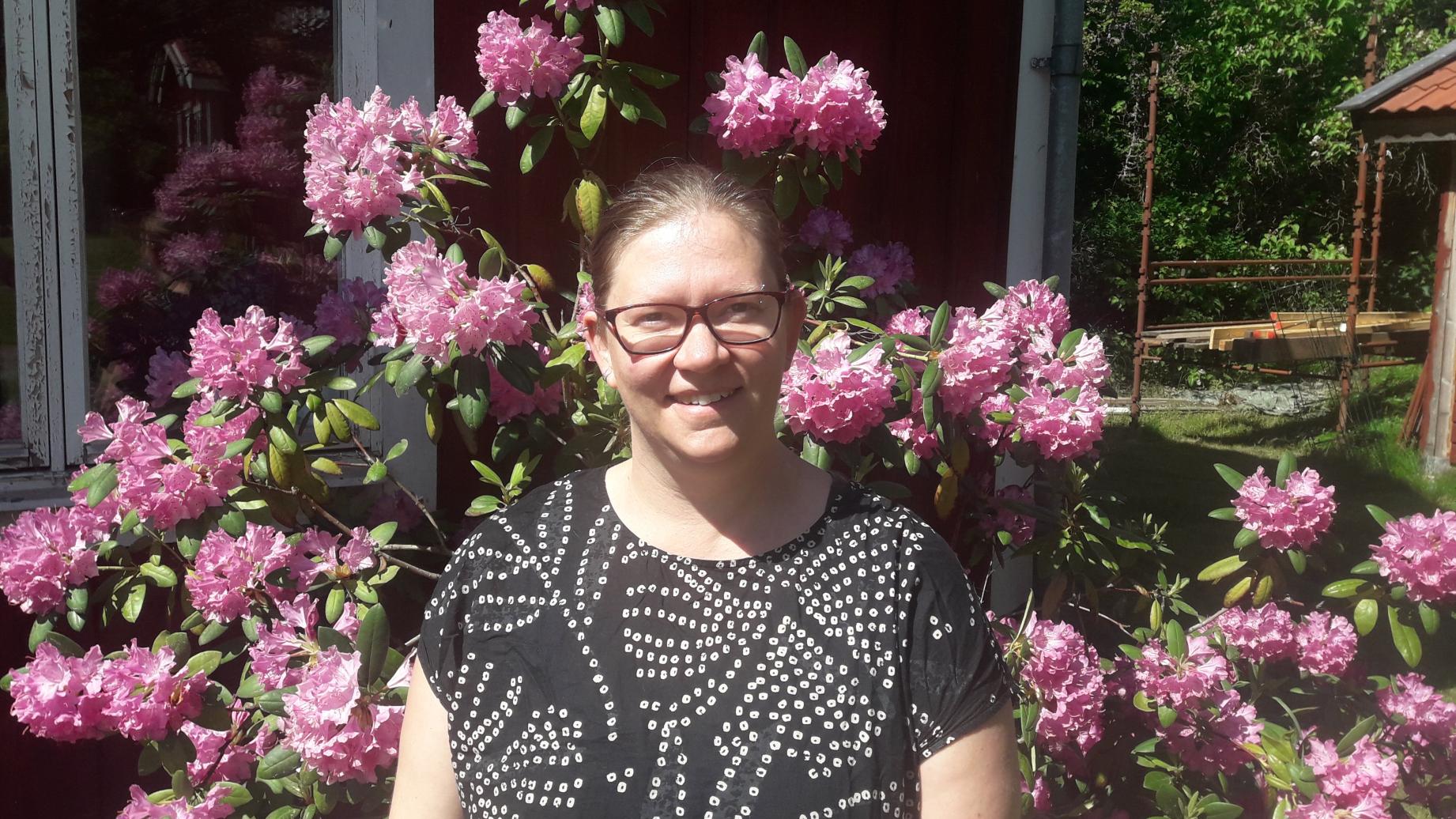 Kvinna med uppsatt hår och glasögon utomhus framför en lila rododendronbuske, foto