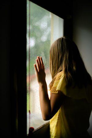 kvinna i gul tröja som tittar ut genom ett fönster