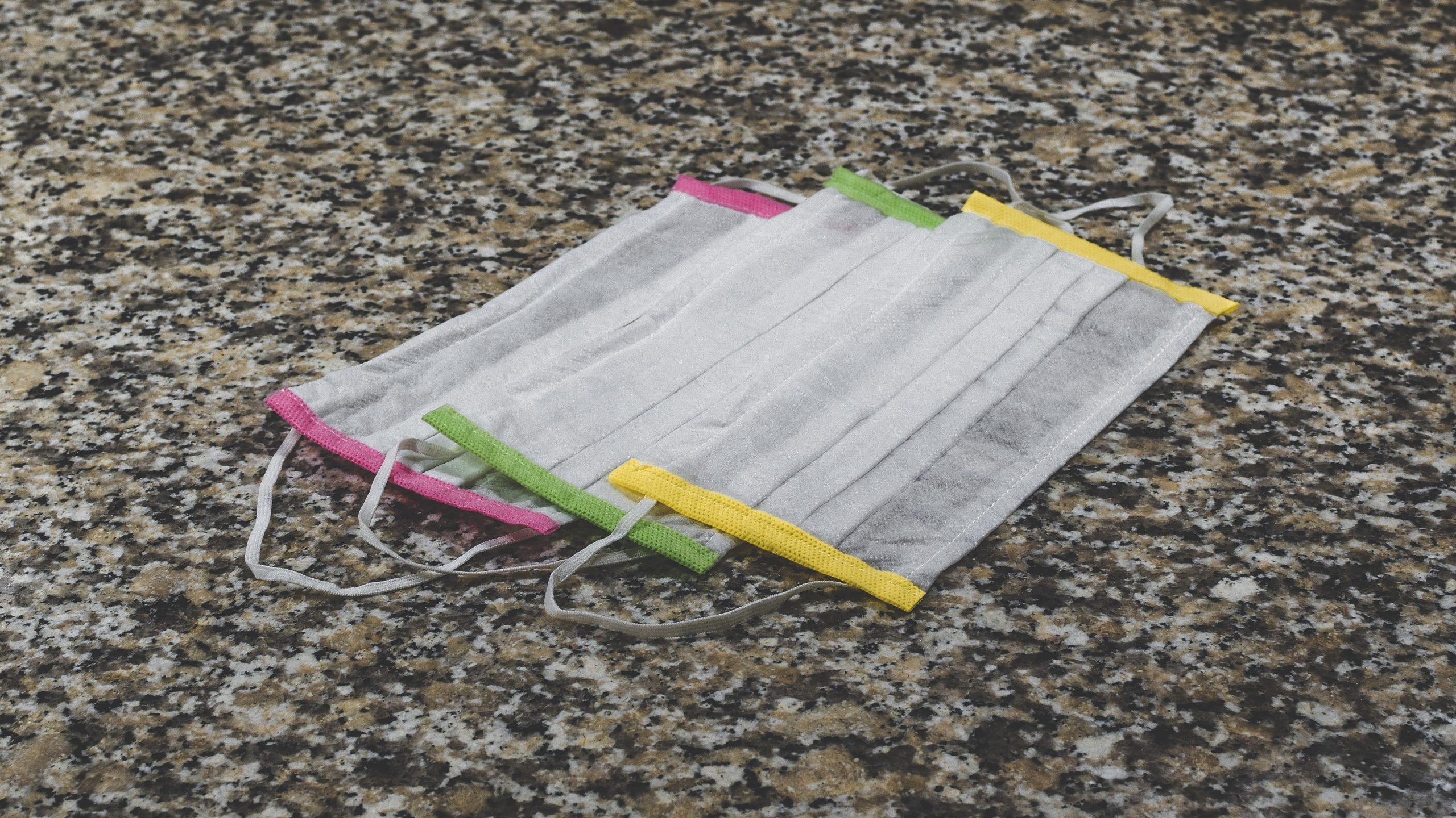 Foto: Tre munskydd med färgglada kanter som ligger på marken