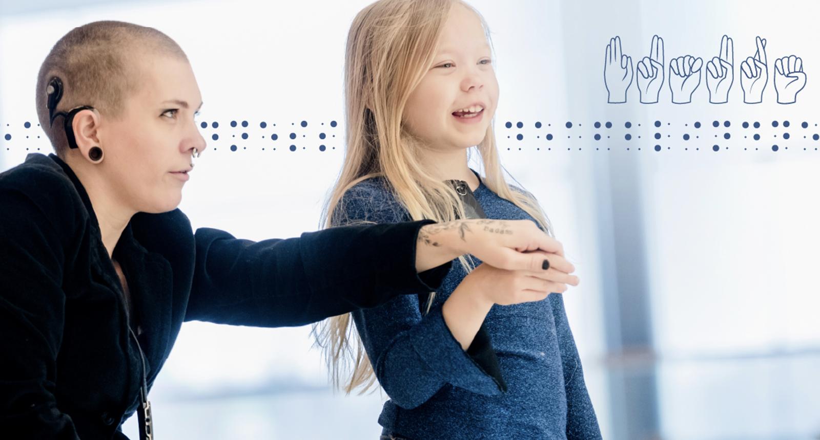 En kvinna med hörappart snett bakom en flicka med blå tröja som kommunicerar med händerna