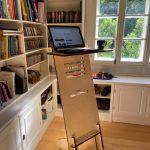Laptop-dator uppställd på ett ståbord i ett rum med bokyllor och ett fönster, foto.