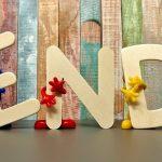 """Foto: Ordet """"End"""" prytt med blommor och uppställt på en scen framför ett träplank."""