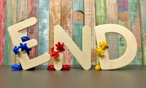 """Ordet """"End"""" prytt med blommor och uppställt på en scen framför ett träplank."""