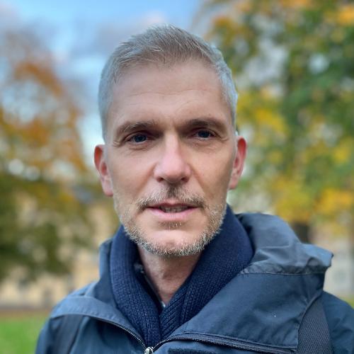Mattias Ehn porträtterad utomhus i blå jacka, foto.